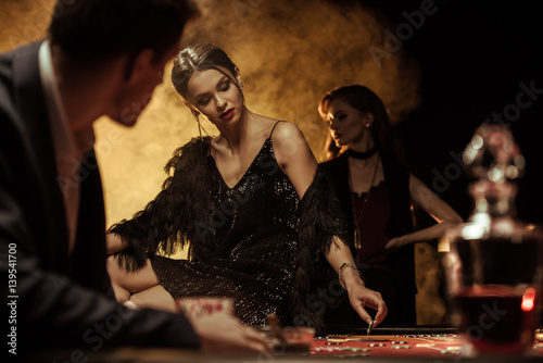 Leinwand Poster Man looking at beautiful woman sitting on poker table in casino