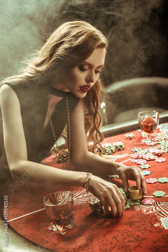 portrait of focused woman counting poker chips плакат
