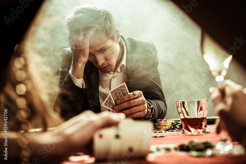 фотография  portrait of upset man looking at poker cards in hand