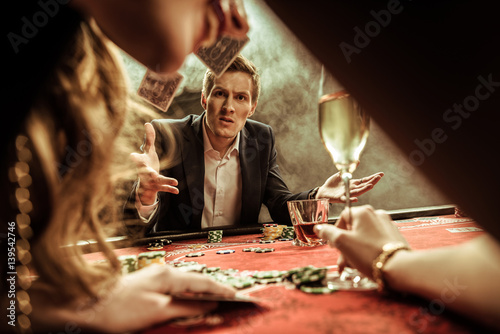 angry man throwing cards while playing poker плакат