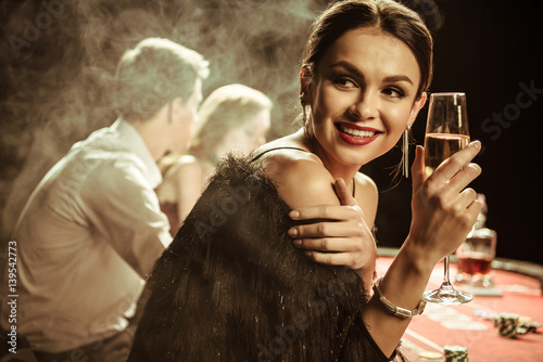 portrait of smiling woman with drink playing poker плакат