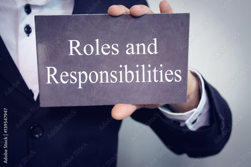 Fototapeta Roles and Responsibilities - Businessman holding chalkboard with text.