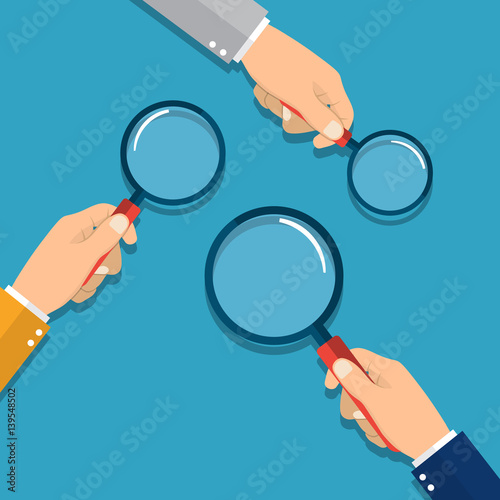 Photo hands holding a magnifying glass