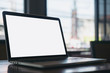 Mockup image of laptop with blank white screen on wooden table in modern loft cafe
