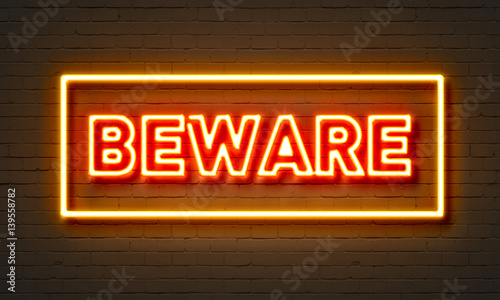 Photo Beware neon sign on brick wall background.