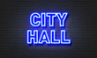 City hall neon sign on brick wall background.