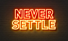 Never Settle Neon Sign On Brick Wall Background.
