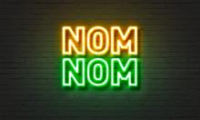 Nom Nom Neon Sign On Brick Wall Background.