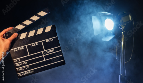 Operator holding clapperboard, studio light on background