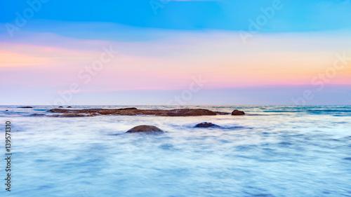 Wall Murals Light pink Long exposure shot of calmness sea and the rock in beautiful sunset sky