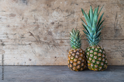 Fotografia  Ripe pineapples on a wooden table
