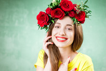 Colorful Portrait Of A Beautiful Woman In Yellow T-shirt With Wreath Made Of Red Roses On The Green Background