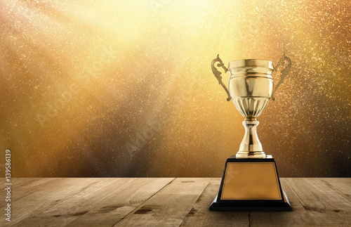 Champion Golden Trophy On Wood Table With Copy Space And Gold Twinkly Lights Glitter Stars