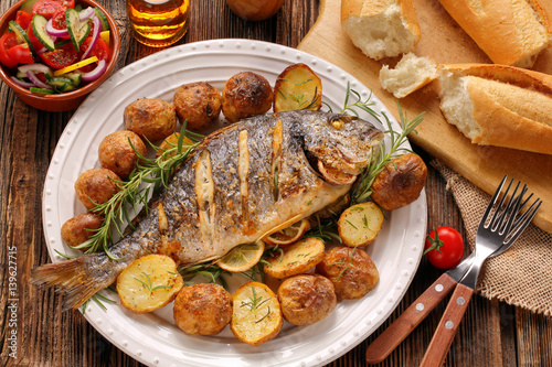 Foto auf Gartenposter Fisch Grilled fish with baguette and vegetables on the plate