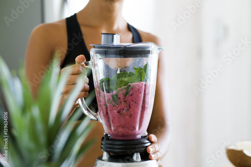 Fotografie, Tablou Woman blending spinach, berries, bananas and almond milk to make a healthy green