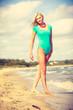 Woman walking on beach wearing swimsuit