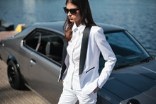 Mafia Lady Outside Japonese Car In The Sea Port. Fashion Girl Standing Next To A Retro Sport Car On The Sun. Stylish Woman In A White Suit And Sunglasses Waiting Near Classic Car.