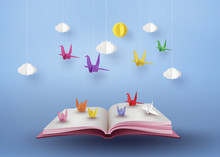 Origami Made Colorful Paper Bird Flying Over Open Book