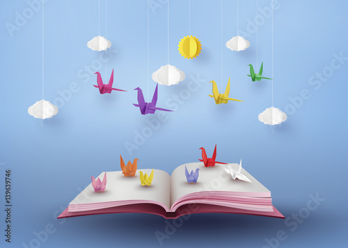 Photo  origami made colorful paper bird flying over open book