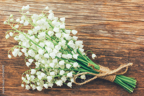 Muguet de mai Vintage bouquet of wild flowers, the white scented lilies of the valley on an old wooden plank closeup