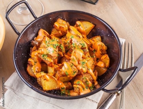 Valokuvatapetti Patatas bravas, spicy potatoes, a typical Spanish dish with fried potato cubes and a spicy garlic sauce
