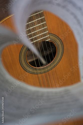 zapis-nutowy-ulozony-w-serce-z-brazowa-gitara-w-tle