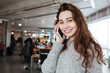 Cheerful woman standing and talkign on mobile phone