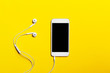 canvas print picture - Close-up of smart phone with headphones on a yellow background. (Top view). Listen to music.