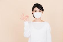 マスクをしてOKサインをする女性