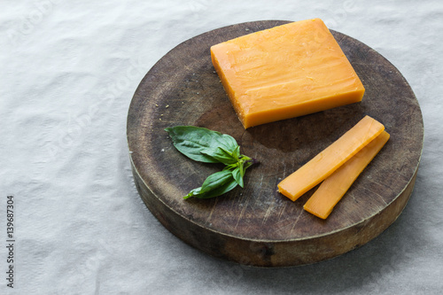 Block cheddar cheese, slices and basil leaves on cutting board