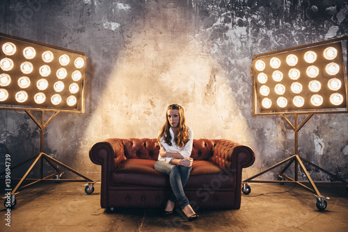 Photo  Girl actress on the couch in the light of soffits