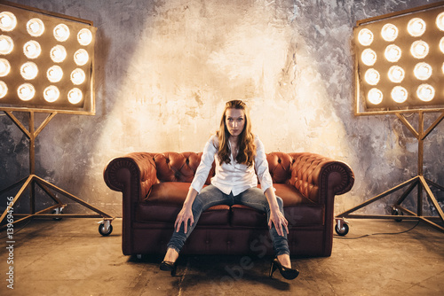 Valokuva Girl actress on the couch in the light of soffits