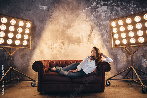 Fotografia, Obraz  Girl actress on the couch in the light of soffits