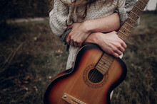 Man With Guitar Hugging His Boho Gypsy Woman In Windy Field. Atmospheric Sensual Moment. Stylish Hipster Couple In Fashionable Look. Rustic Wedding Concept
