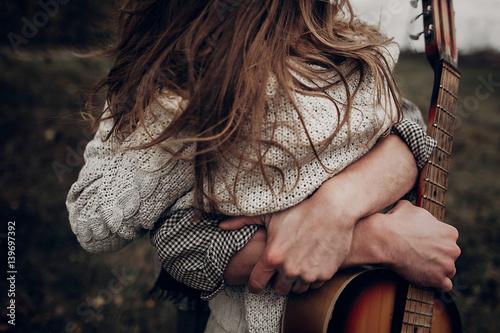Fotografie, Obraz  man with guitar hugging his boho gypsy woman closeup in windy field