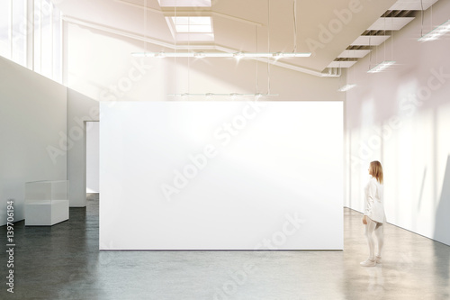 Fotografia Woman walking near blank white wall mockup in modern gallery