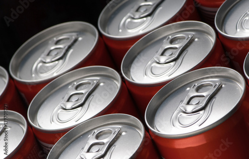 group of red can tins close up on a black background Poster
