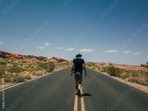 Papiers peints Route 66 A handsome young tourist walking in the middle of the road on the hot summer day in valley of fire national park
