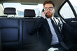 Young serious businessman sitting in car and talking on phone