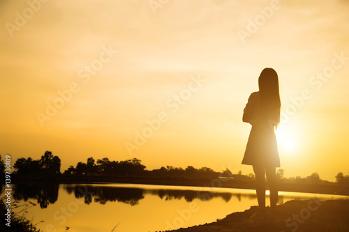 Silhouette of woman praying over beautiful sky background Fototapet