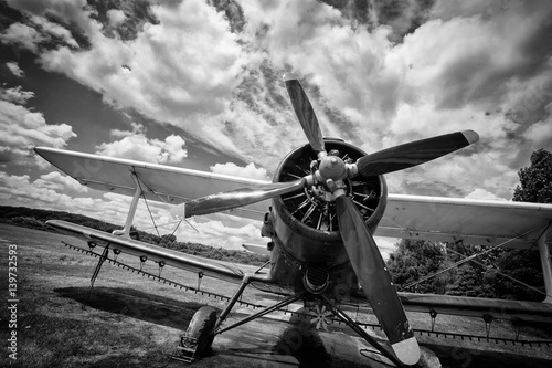 Old airplane on field in black and white Canvas Print