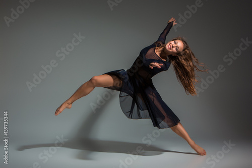 Dancing woman in a black dress. Contemporary modern dance on a gray background.