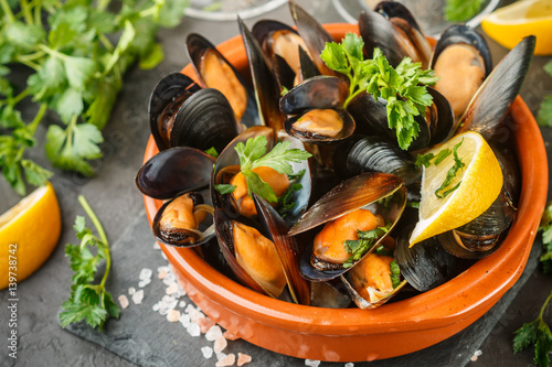 Fotobehang Schaaldieren Mussels in wine with parsley and lemon. Seafood. Clams in the shells. Delicious snack for gourmands. Selective focus