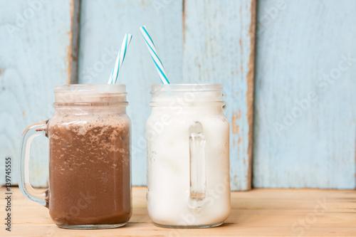 Foto op Plexiglas Milkshake Milkshake put on wooden in blue wall room. Pastel tone.
