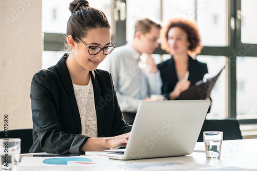 Hard-working young woman analyzing business information