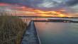 Sonnenaufgang am Neusiedlersee mit Steg und Schilf