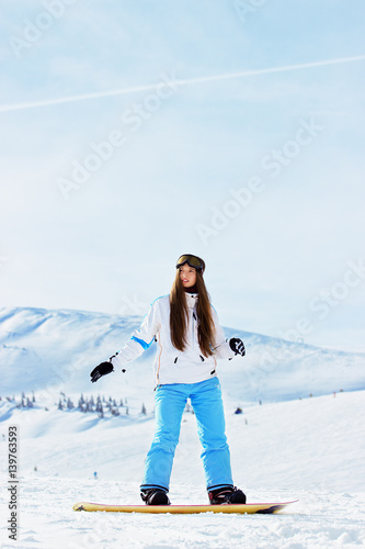 Fotobehang Wintersporten Young beautiful girl in white jacket, blue ski pants and googles on her head riding on snowboard in the snowy mountains. Winter sports.