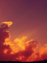 Cielo rosso al tramonto con raggi di sole che spuntano dietro ad una nuvola