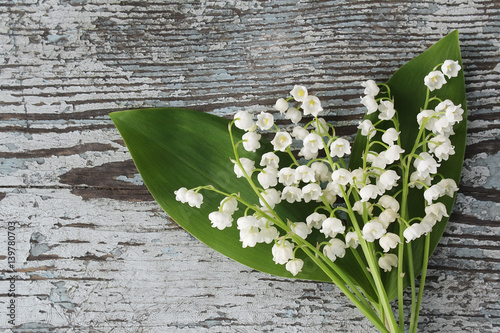 Wall Murals Lily of the valley Bouquet of lilies of the valley on an old wooden background