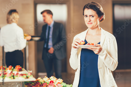 Disgusted Woman Tasting Snacks at Buffet Reception Fototapet